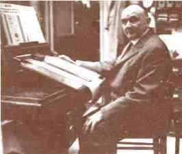 Eugene DeRoy at his arranging table laying out musical notes, trapwork effects and register controls for a Symphonia music roll.
