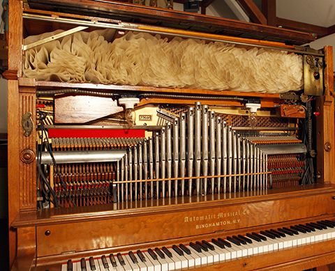 Upper section of Automatic Musical Company transitional piano with metal flute pipes.