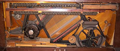 Early rotary pump and other mechanisms below the keytbed in an Automatic Musical Company Mandolin Piano.