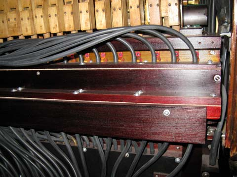 Early Seeburg style J with red shellac finish on the pneumatic components above the keyboard.