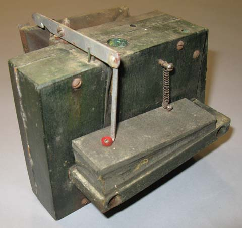 "Back view of the latch bar and ""play"" pneumatic on the back of an early style rewind box."